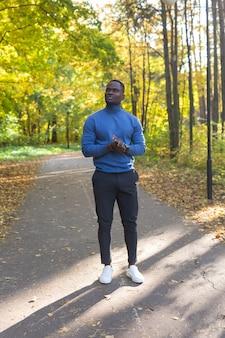 Fröhlicher junger afroamerikaner junger mann in den stilvollen kleidern geht im herbstpark am sonnigen warmen herbsttag