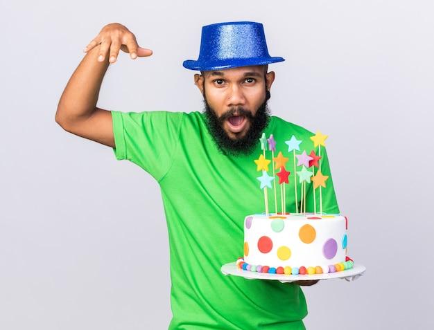 Fröhlicher junger afroamerikanischer kerl mit partyhut, der kuchen hält, der die hand hebt