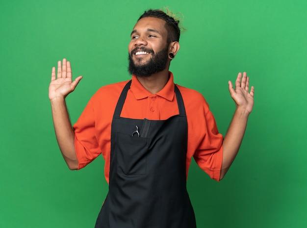 Fröhlicher junger afroamerikanischer männlicher friseur in uniform, der auf die seite schaut und leere hände isoliert auf grüner wand zeigt