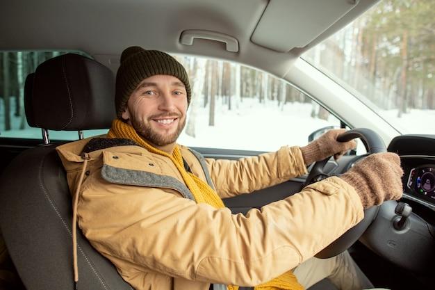 Fröhlicher junger aktiver mann in warmer winterkleidung, der sie mit einem zahnigen lächeln ansieht, während er am steuer sitzt und zu seinem landhaus fährt