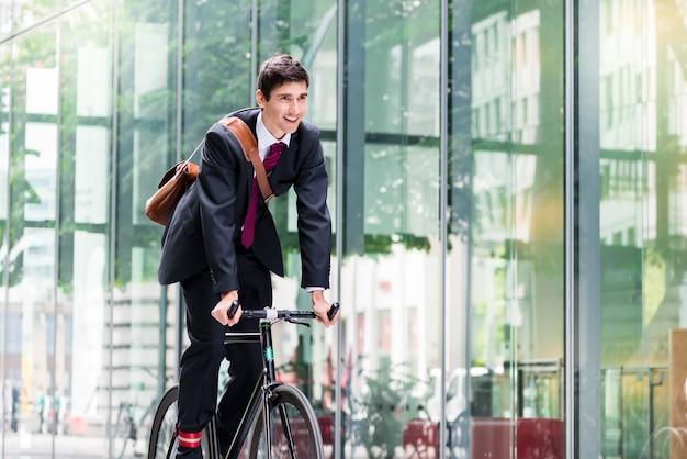 Fröhlicher junger angestellter mit einem gesunden lebensstil, der ein nutzfahrrad zu einem modernen arbeitsplatz in berlin fährt