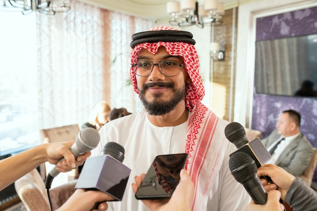 Fröhlicher junger arabischer männlicher delegierter, der mit mikrofonen vor journalisten steht und ihre fragen während des interviews beantwortet