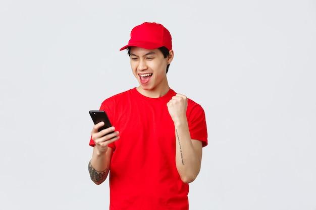 Fröhlicher junger asiatischer lieferbote in rotem, einheitlichem t-shirt und mütze, der gute nachrichten auf dem smartphone-bildschirm liest, macht faustpumpe, die große boni oder erfolg singt. kurier sagen ja, bestellungen verfolgen