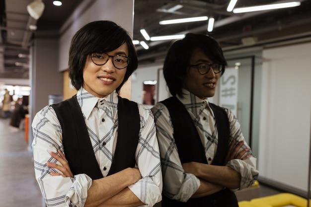 Fröhlicher junger asiatischer mann, der brille trägt, die mit verschränkten armen steht