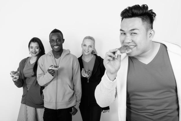 Fröhlicher junger asiatischer mann, der ein stück pizza isst, mit einer verschiedenen gruppe von multiethnischen freunden, die lächeln und ein stück pizza zusammenhalten?