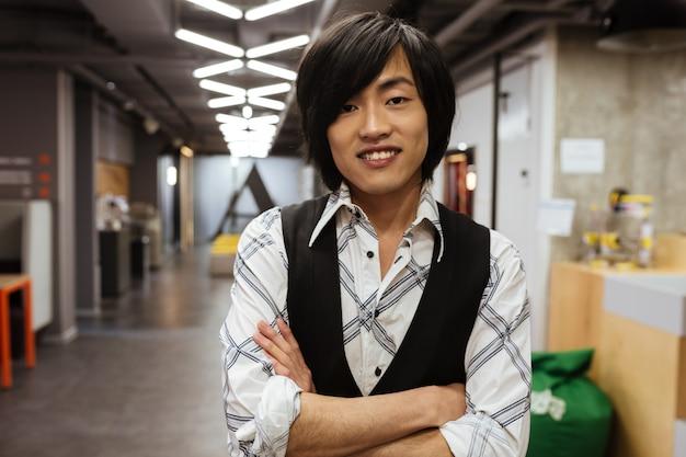 Fröhlicher junger asiatischer mann, der kamera betrachtet. coworking-konzept.