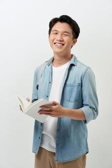 Fröhlicher junger asiatischer student mit einem buch