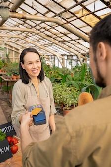Fröhlicher junger asiatischer verkäufer im vorfeld, der zahlungsterminal an kunden übergibt, der mit nfc-karte für bio-produkte im bauernmarkt zahlt