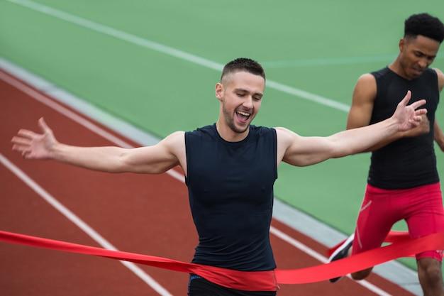Fröhlicher junger athletenmann, der ziellinie überquert