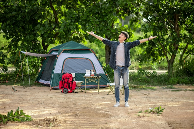 Fröhlicher junger backpacker-mann, der vor dem zelt im wald mit kaffeeset steht und offene arme hat und während des campingausflugs im sommerurlaub frische kaffeemühle zubereitet