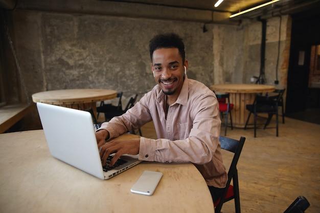 Fröhlicher junger bärtiger dunkelhäutiger mann in freizeitkleidung, der über dem coworking space sitzt, die kamera mit einem breiten, charmanten lächeln betrachtet und die hände am schlüsselbund seines modernen laptops hält
