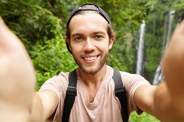 Fröhlicher junger bärtiger hipster, der baseballmütze trägt, die selfie in seinen ferien im exotischen land nimmt