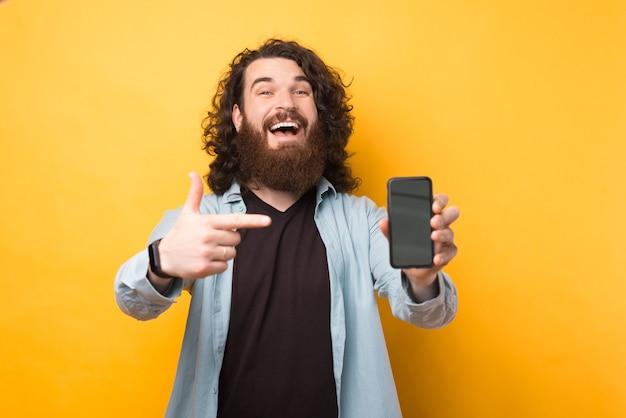 Fröhlicher junger bärtiger hipster-mann, der auf smartphone über gelbem hintergrund zeigt