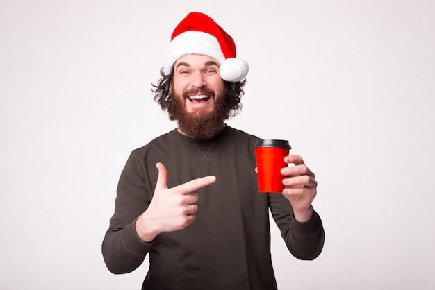 Fröhlicher junger bärtiger mann, der auf rote tasse kaffee zeigt und weihnachtsmannhut trägt