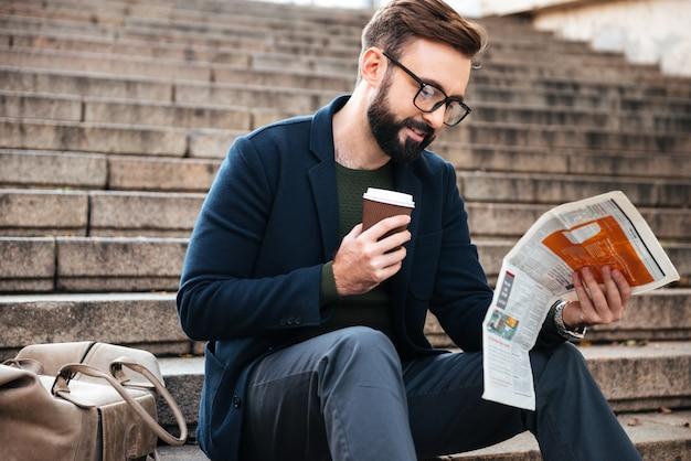Fröhlicher junger bärtiger mann, der draußen auf stufen sitzt, die zeitung lesen