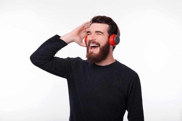 Fröhlicher junger bärtiger mann hört musik in seinen kopfhörern und singt auf leerraum.