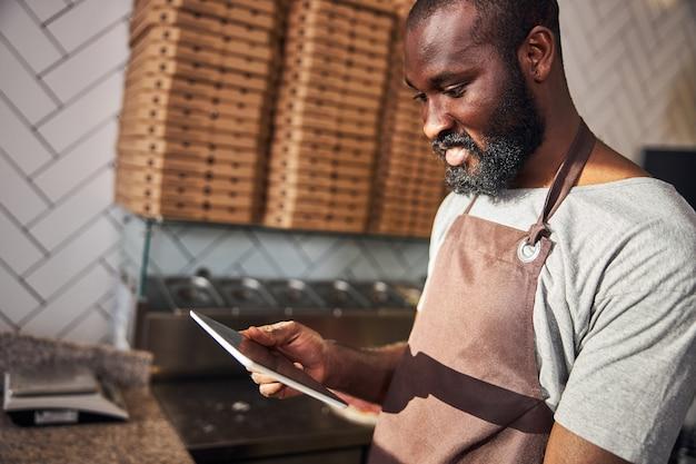 Fröhlicher junger bärtiger mann macht pizza in der professionellen küche und nutzt das internet auf dem touchpad