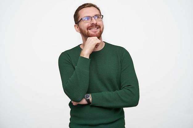 Fröhlicher junger bärtiger mann mit braunen kurzen haaren, der beim posieren eine brille trägt, die hand an sein kinn hebt und positiv lächelt, während er nach oben schaut