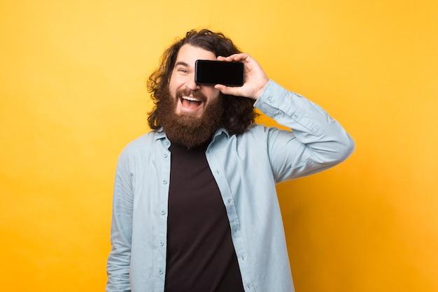 Fröhlicher junger bärtiger mann mit langen haaren, der smartphone über dem auge hält und über gelbem hintergrund lächelt