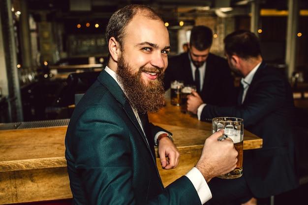 Fröhlicher junger bärtiger mann schauen auf kamera und lächeln. er hält einen krug bier in der hand. zwei andere leute stehen dahinter und reden.
