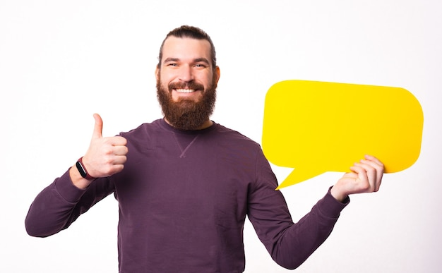 Fröhlicher junger bärtiger mann zeigt einen daumen hoch und hält eine sprechblase und lächelt