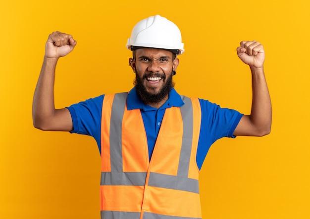 Fröhlicher junger baumeister in uniform mit schutzhelm, der mit erhobenen fäusten isoliert auf oranger wand mit kopierraum steht