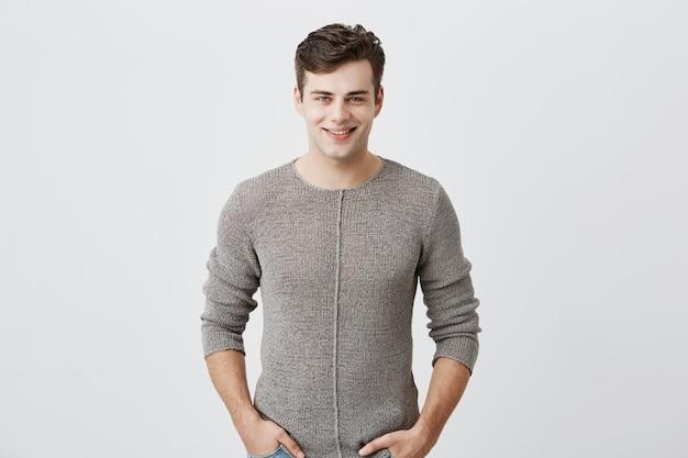 Fröhlicher junger blauäugiger mann mit dunklem haar, der im studio mit glücklichem lächeln aufwirft, gutaussehender mann, der lässig gekleidet ist und freudig lächelt und seine weißen geraden zähne zeigt. positives emotionskonzept.