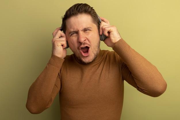 Fröhlicher junger blonder gutaussehender mann, der kopfhörer trägt und greift und musik genießt