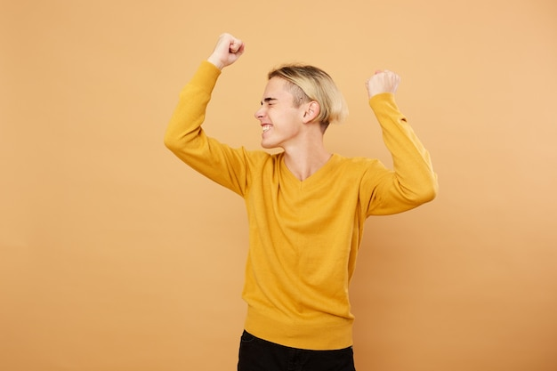 Fröhlicher junger blonder kerl in gelbem pullover posiert im studio auf dem beigefarbenen hintergrund.