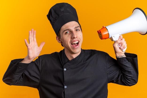 Fröhlicher junger blonder männlicher koch in kochuniform und mütze mit lautsprecher und leerer hand
