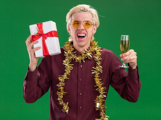 Fröhlicher junger blonder mann mit brille mit lametta-girlande um den hals, der ein glas champagner und ein geschenkpaket hält und auf die kamera schaut, die isoliert auf grünem hintergrund schreit