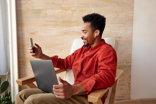 Fröhlicher junger brünetter dunkelhäutiger mann mit bart, der gerne lächelt, während er einen videoanruf tätigt und mit seinem laptop aus der ferne an der inneneinrichtung arbeitet
