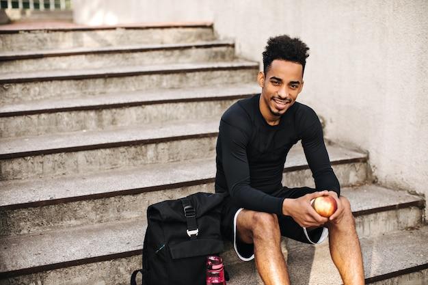 Fröhlicher junger brünetter mann in langärmeligem sport-t-shirt und shorts sitzt draußen auf der treppe
