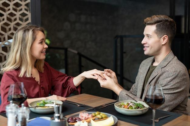 Fröhlicher junger eleganter mann, der seine hübsche freundin mit einem lächeln ansieht, während er beim abendessen den verlobungsring über den servierten tisch legt