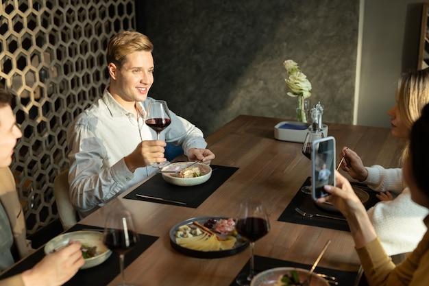 Fröhlicher junger eleganter mann mit einem glas rotwein, der zum abendessen toast macht, während er am servierten tisch in einem modernen restaurant unter freunden sitzt?