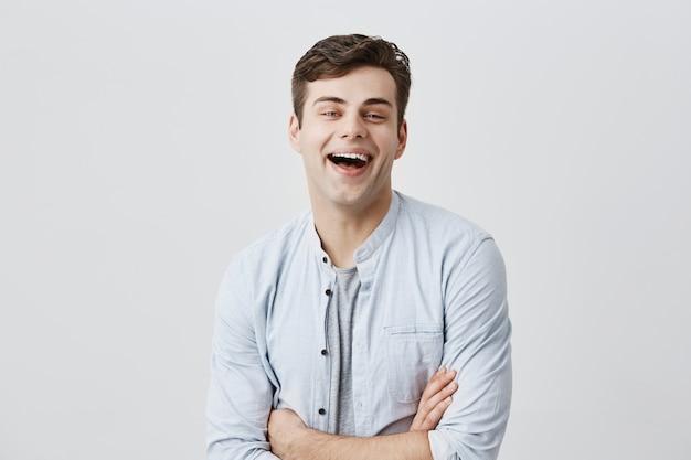 Fröhlicher junger europäer, der breit mit den zähnen lächelt, sich über positive nachrichten oder beförderung bei der arbeit freut und die arme verschränkt hält. menschliche emotionen, gefühle, haltung und reaktion