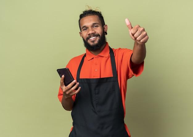 Fröhlicher junger friseur in uniform, der nach vorne schaut und das mobiltelefon mit dem daumen nach oben zeigt, isoliert auf olivgrüner wand mit kopierraum