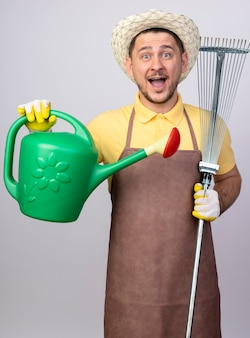 Fröhlicher junger gärtnermann, der overall und hut in arbeitshandschuhen hält, die gießkanne und rechen halten, die vorne lächelnd mit glücklichem gesicht über weißer wand stehen