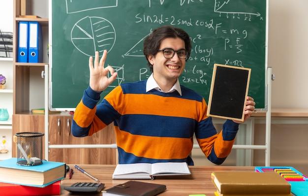 Fröhlicher junger geometrielehrer mit brille, der am schreibtisch mit schulmaterial im klassenzimmer sitzt und eine mini-tafel zeigt, die nach vorne schaut und ein gutes zeichen zeigt