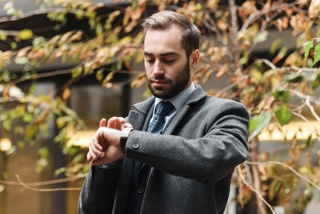 Fröhlicher junger geschäftsmann, der anzug trägt, der draußen geht und zeit überprüft