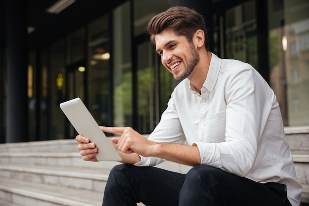 Fröhlicher junger geschäftsmann, der auf treppen sitzt und tablet im freien benutzt using