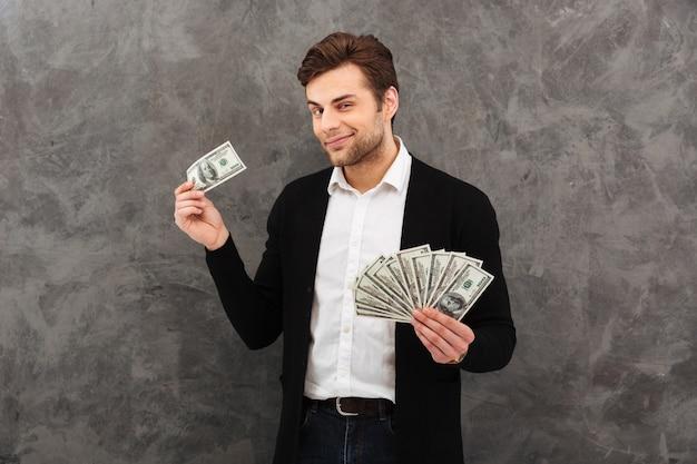 Fröhlicher junger geschäftsmann, der geld hält