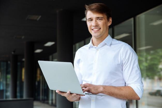 Fröhlicher junger geschäftsmann, der laptop hält und auf handy nahe geschäftszentrum spricht