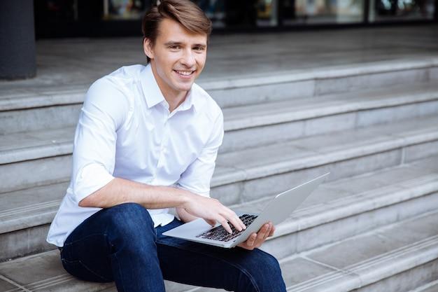 Fröhlicher junger geschäftsmann, der laptop nahe geschäftszentrum benutzt