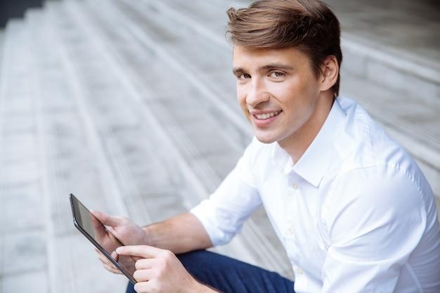 Fröhlicher junger geschäftsmann, der tablette nahe geschäftszentrum benutzt