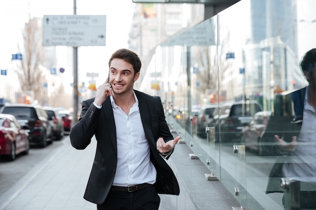 Fröhlicher junger geschäftsmann, der telefonisch nahe geschäftszentrum spricht