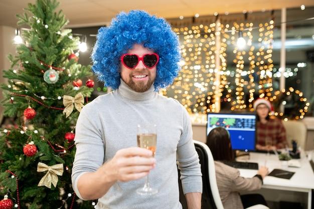 Fröhlicher junger geschäftsmann in der blauen lockigen perücke, die mit champagnerflöte durch geschmückten weihnachtsbaum im büro röstet