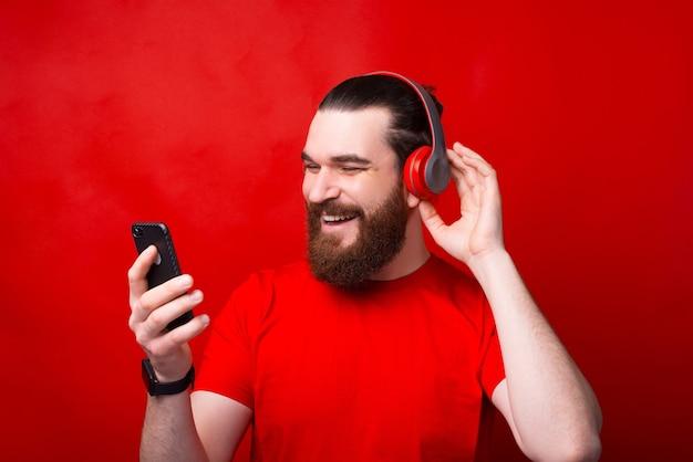 Fröhlicher junger glücklicher bärtiger mann, der musik über rote wand hört