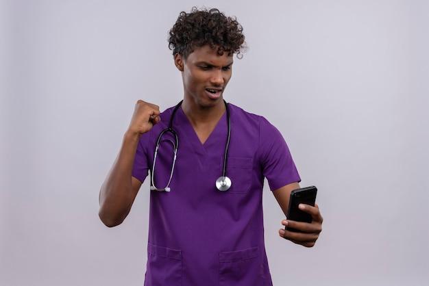 Fröhlicher junger gutaussehender dunkelhäutiger männlicher arzt mit lockigem haar in violetter uniform mit stethoskop, der sein smartphone mit geballter faust betrachtet