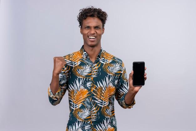 Fröhlicher junger gutaussehender dunkelhäutiger mann mit lockigem haar im blatt bedruckten hemd, das smartphone mit geballter faust hält